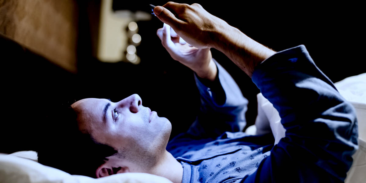 MAN IN BED ON PHONE
