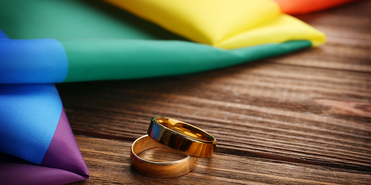 WEDDING RINGS AND RAINBOW GAY FLAG