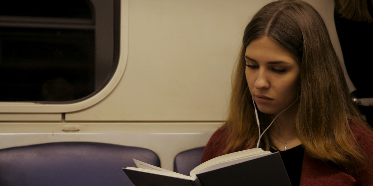girl reading a book in subway